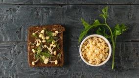 面包片用发芽的豆和南瓜籽与一束荷兰芹在一张黑木桌上 r 免版税库存图片