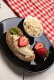 面包片用白色乳酪和草莓在上面 免版税库存图片
