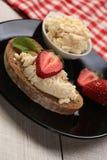 面包片用白色乳酪和草莓在上面 库存照片