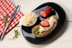 面包片用白色乳酪和草莓在上面 免版税库存照片