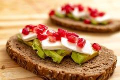 面包片用鲕梨、西红柿、石榴种子和新鲜的干酪 免版税库存图片