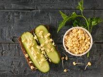 面包片用黄瓜和发芽的绿豆在一张黑暗的木桌上 免版税库存图片