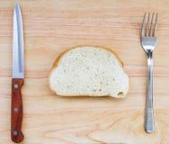 面包片的图象在一张木桌上的与叉子和刀子 库存图片