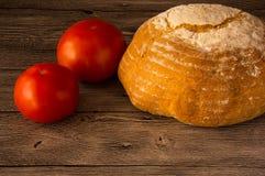 面包用在一张木桌上的蕃茄 免版税图库摄影