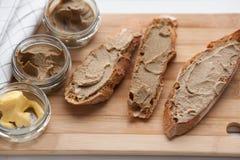 面包用小牛肉和兔子头脑用在一个竹委员会的黄油 顶视图 免版税库存照片