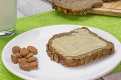 面包用杏仁黄油和牛奶 免版税库存照片