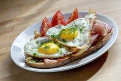 面包用火腿和煎蛋装饰用在板材的香葱 免版税库存照片