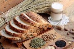 黑面包用整个五谷谷物切和牛奶 免版税库存照片