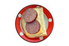 面包用黄油,乳酪,在红白的陶器的香肠我 免版税库存照片