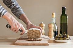 面包由女性手切开了在厨房里 免版税库存照片