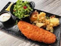 面包白色鱼用土豆和新鲜的莴苣沙拉 库存照片