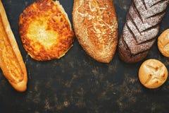 面包的一汇集与洒和乳酪的在土气黑暗的背景 复制空间,顶视图 免版税图库摄影
