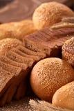 面包的Assortement在粗麻布的在木桌上 面包片和卷 库存照片