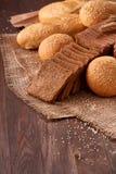 面包的Assortement在粗麻布的在木桌上 面包片和卷 图库摄影