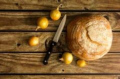 面包,葱,在桌上的刀子 在视图之上 免版税库存图片