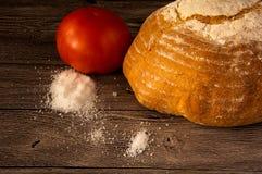 面包,蕃茄,在一张木桌上的盐 图库摄影