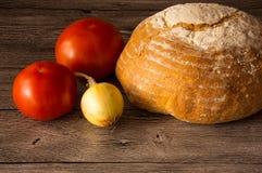面包,蕃茄,在一张木桌上的葱 免版税库存图片