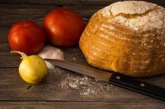 面包,蕃茄,葱,盐,在一张木桌上的刀子 免版税库存照片