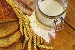 面包,面包片,五谷的小麦面粉和耳朵在木背景的 土气和农村概念 关闭 平的位置 库存照片