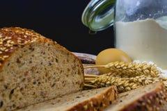面包,面包片,小麦面粉、五谷的鸡蛋和耳朵在木背景的 土气和农村概念 关闭 复制 库存图片