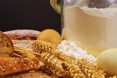 面包,面包片,小麦面粉、五谷的鸡蛋和耳朵在木背景的 土气和农村概念 关闭 复制 免版税库存图片