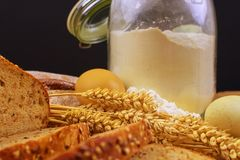 面包,面包片,小麦面粉、五谷的鸡蛋和耳朵在木背景的 土气和农村概念 关闭 复制 免版税库存照片
