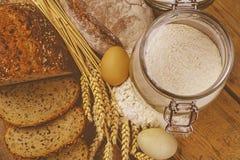 面包,面包片,小麦面粉、五谷的鸡蛋和耳朵在木背景的 土气和农村概念 关闭 平面 库存照片