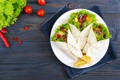 面卷饼用切好的肉,鲕梨,菜,在一块板材的辣椒在黑暗的木背景 免版税库存图片