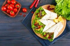 面卷饼用切好的肉,鲕梨,菜,在一块板材的辣椒在黑暗的木背景 库存照片