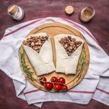 面卷饼用肉和菜在一个切板用蕃茄和大蒜在餐巾木土气背景顶视图 库存图片
