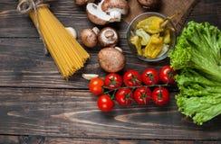 面团、蕃茄、沙拉、胡椒、食谱蘑菇和书在木桌背景的 免版税库存图片