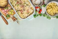 面团在乳脂状的调味汁的砂锅用romanesco圆白菜和火腿准备好为在与成份的厨房用桌背景烘烤,顶面v 库存照片