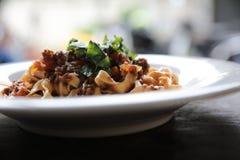 面团意大利细面条博洛涅塞用牛肉和西红柿酱在木背景 免版税库存照片