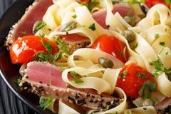 面团意大利细面条用宏观金枪鱼排、的蕃茄和的雀跃 贺尔 库存照片