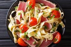 面团意大利细面条用宏观金枪鱼排、的蕃茄和的雀跃 顶层 库存照片