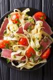 面团意大利细面条用宏观金枪鱼排、的蕃茄和的雀跃 顶层 库存图片