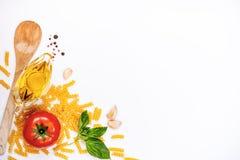 面团成份顶视图在白色背景-未加工的fusilli、新鲜的蓬蒿、拨蒜、橄榄油和成熟tomatoe的 意大利语 免版税库存照片