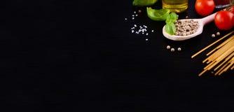 面团成份-蕃茄、橄榄油、大蒜、意大利草本、新鲜的蓬蒿和意粉在黑石背景 免版税库存图片