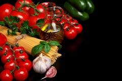 面团未加工在黑色用蕃茄,橄榄油,大蒜离开 免版税库存图片