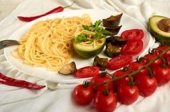 面团用油煎的茄子、蕃茄和绿色鲕梨装饰用西红柿,辣椒和叉子 库存图片