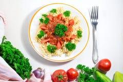 面团用西红柿酱和叉子板材与成份的烹调的在白色背景,与拷贝空间的顶视图 免版税库存照片