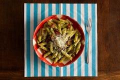 面团用pesto调味汁,在方格花布板材,绿松石休息的巴马干酪 免版税图库摄影