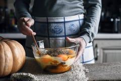面团的成份做南瓜在玻璃碗的转储蛋糕 免版税库存图片