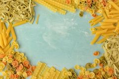 面团的美好的构成与空间的文本的 Penne, Mafalde, Tagliatelle,意粉在蓝色的一个框架排行了 免版税库存图片