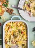 面团砂锅用romanesco圆白菜和火腿在乳脂状的调味汁,供食在板材有叉子的在厨房用桌上与成份,冠上 图库摄影