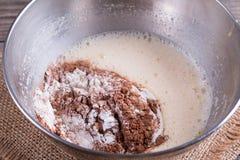 面团/面团为绉纱或薄煎饼做准备用小麦面粉和可可粉在碗、牛奶、鸡蛋和油 库存图片