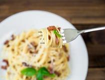 面团Carbonara和意粉板材用烟肉和帕尔马干酪在一把叉子在老木桌上 库存图片