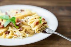 面团Carbonara和意粉板材用烟肉和帕尔马干酪在一把叉子在老木桌上 库存照片