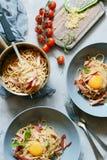 面团carbonara用烟肉和巴马干酪在灰色板材在桌上,餐馆服务 alla茄子背景烹调新鲜的意大利norma荷兰芹意大利面食意粉蕃茄传统白色 库存照片