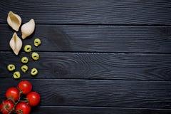 面团conchiglie和意大利式饺子 红色樱桃tomatoeson黑色bac 库存照片